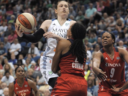 Minnesota Lynx guard Lindsey Whalen, left, goes to the basket against Washington Mystics forward Monique Currie, center, during the second quarter of a WNBA basketball game Friday, June 20, 2014, in Minneapolis.