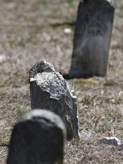 A line of stone headstones are shown at the Marlboro Psychiatric Hospital cemetery.