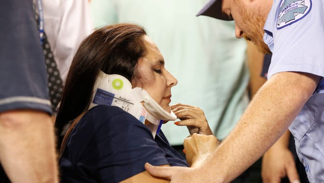 Comerica Park medical personnel administer to a female fan who was hit by a foul ball in the first row in back of the Detroit Tigers  dugout in the eighth inning of their baseball game against the Texas Rangers on Friday, August 21, 2015, in Detroit.