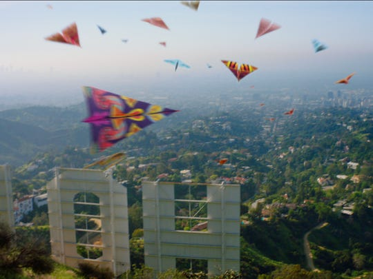 Paper airplanes float over the iconic Hollywood sign