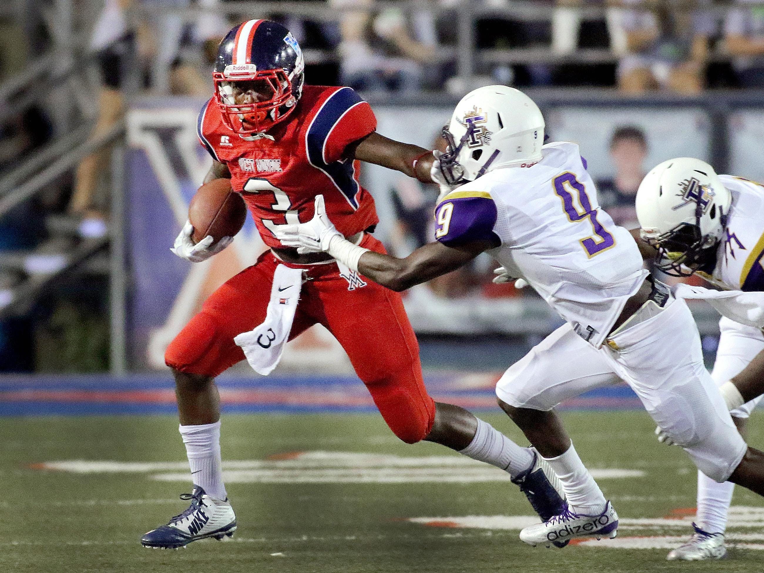 West Monroe RB Trey Coleman (3) stiff-arms Franklinton defender Martavious James (9) Friday night in high school action at Don Shows Field at Rebel Stadium.