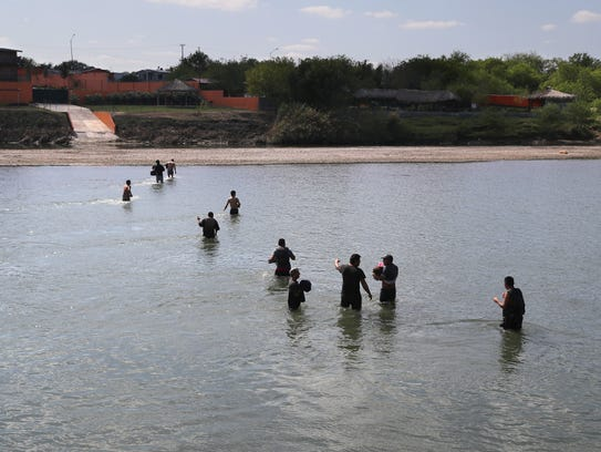 A group of undocumented immigrants wade across the