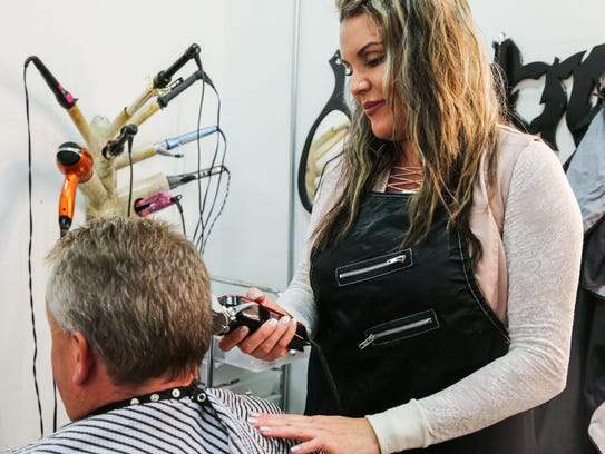 Autumn Brockman cuts Mike O'Connor's hair Tuesday,
