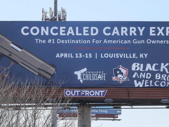 "A vandalized billboard with the graffiti tag ""Resist 45."""