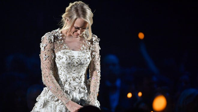 """Carrie Underwood gets emotional after singing """"Softly and Tenderly"""" in a tribute to the Las Vegas shooting victims and members of the country community who passed away in the last year during the CMA Awards Wednesday, Nov. 8, 2017 at Bridgestone Arena in Nashville, Tenn."""