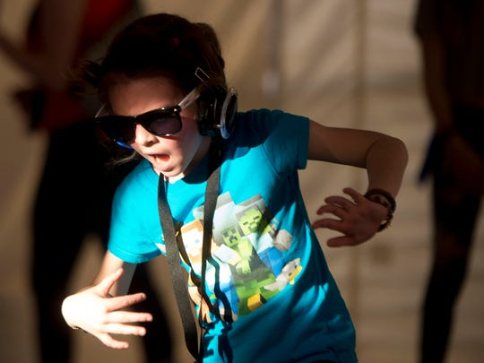 A young dancer has fun inside the silent disco tent