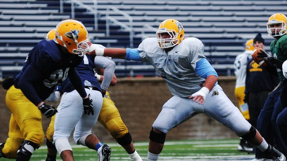 Augustana's #73 Sam Lee, white jersey, participates in a drill during a football practice at Kirkeby-Over Stadium in Sioux Falls Tuesday, Oct. 22, 2013. (Joe Ahlquist / Argus Leader)