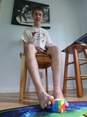 Daniel Rose-Levine practices solving a Rubik's cube