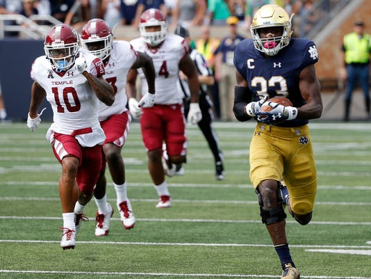 FILE - In this Sept. 2, 2017, file photo, Notre Dame running back Josh Adams runs down the sideline the team's NCAA college football game against Temple  in South Bend, Ind. The first regular-season AP Top 25 was released Tuesday and while the top was mostly unchanged–save a big drop by No. 10 Florida State–there was some shuffling at the bottom. Among the two newly ranked teams is the bluest of blue bloods: Welcome, No. 24 Notre Dame. Coming off a 4-8 season, the Fighting Irish were third among the others receiving votes in the preseason poll. So it was not too surprising that a 49-16 victory against Temple would lure in some voters. (AP Photo/Charles Rex Arbogast, File)