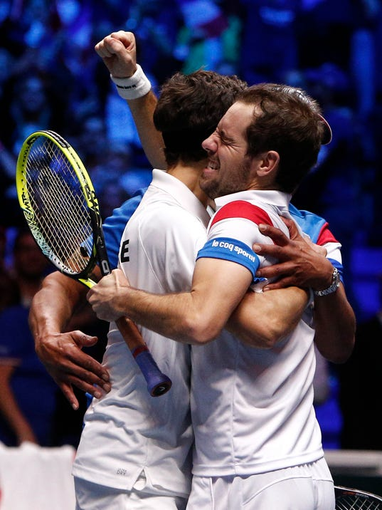 France's Richard Gasquet, right, hugs Pierre-Hugues Herbert after defeating Belgium's Ruben Bemelmans and Joris De Loore in their Davis Cup final double match at the Pierre Mauroy stadium in Lille, northern France, Saturday, Nov. 25, 2017. Gasquet and Herbert won 6-1, 3-6, 7-6 (2), 6-4 to give France a 2-1 lead over Belgium in the Davis Cup final. (AP Photo/Michel Spingler)