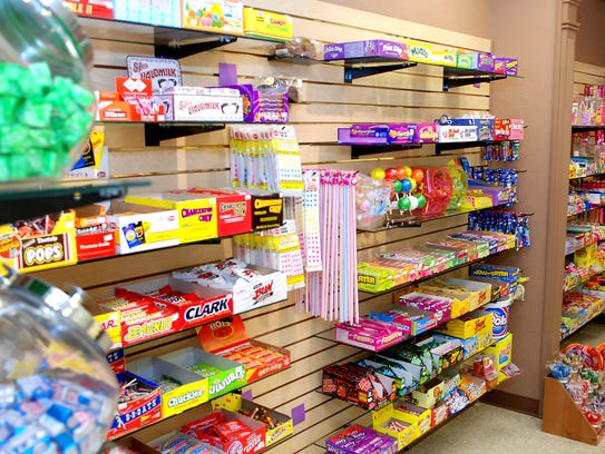 A wall of classic candy dominates one corner of Allo