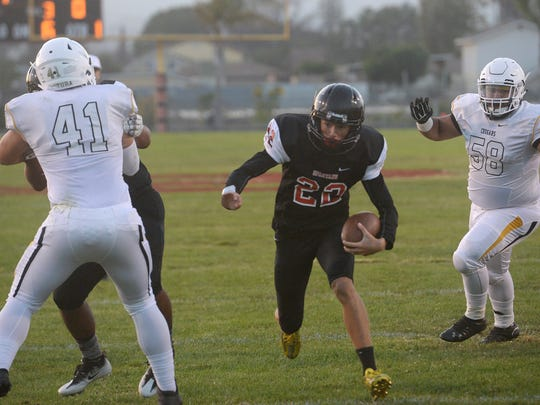 Rio Mesa's JP Arbon finds a hole between Connor McDermott (41) and John Cervantez (58) to run for a touchdown during the Spartans' loss to Ventura on Friday night.