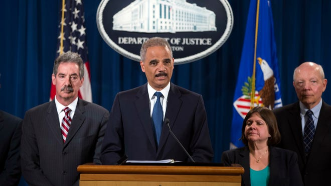 Attorney General Eric Holder, center, speaks during a news conference at the Justice Department Monday in Washington, D.C.. The Justice Department has charged Credit Suisse AG with helping wealthy Americans avoid paying taxes through offshore accounts. From left are Deputy Attorney General James Cole, Holder, Assistant Attorney General for the Tax Division Kathryn Keneally, and IRS Commissioner John Koskinen.