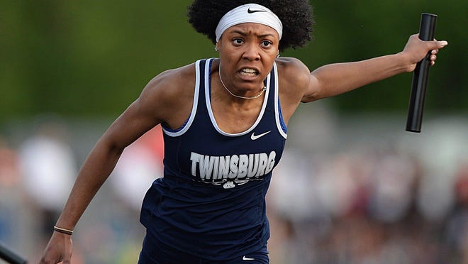 Twinsburg's Alyssa Willis lunges across the finish line in an attempt to cross before Kenston's Elyse Myles in the 400 meter relay race during the Division I regional track meet last season.