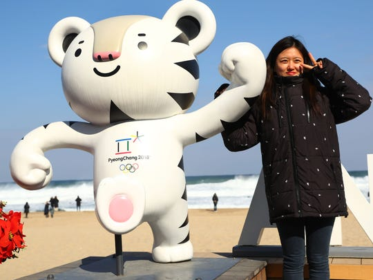 A woman poses with Olympic mascot Soohorang on Anmok Beach at the Sea of Japan at the PyeongChang 2018 Winter Olympic Games.