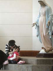 In this Enquirer file photo from 2012, Stephanie Kemplin, of Maineville, embraces her daughter underneath a statue of Mary during Ash Wednesday mass at St. Margaret of York in Loveland.