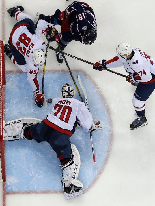 Washington Capitals' Braden Holtby (70) makes a save as teammates Jay Beagle (83) and John Carlson (74) and Columbus Blue Jackets' Pierre-Luc Dubois look for a rebound during the third period of an NHL hockey game Tuesday, Feb. 6, 2018, in Columbus, Ohio. The Capitals won 3-2. (AP Photo/Jay LaPrete)