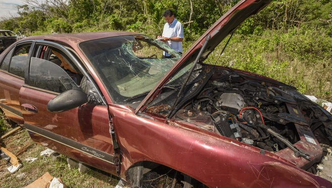 Yigo Mayor Rudy Matanane records the identification numbers on one of 11 vehicles found abandoned along Chalan Bada in Yigo on Thursday, March 16, 2017. Matanane is hoping to use the information to track down the owners of the vehicles illegally dumped at the site. The mayor says he will not tolerate the disposal of automobiles and the increasing amount of trash that have been improperly discarded of in his village.