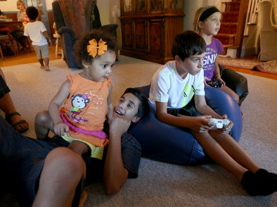 Joey Sundine holds his cousin Hadassah Nerestant while his younger brother Riley Sundine and cousin Eva Lynn Anderson play a video game.