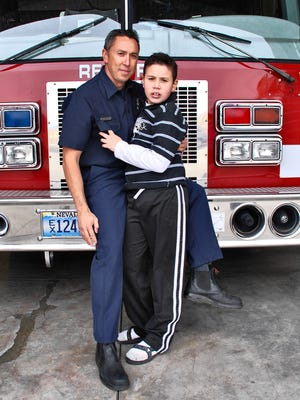 A submitted photo of Art Reitz holding his now 12-year-old son, Justin, while standing in front of a fire truck. The photo was featured on the Firehouse Magazine, a publication focusing on news for firefighters and featured in  fire departments nationwide.