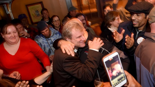 Supporters at the Holy Hound Taproom embrace Michael Helfrich following his victory for York city mayor over C. Kim Bracey on Tuesday, Nov. 7, 2017.