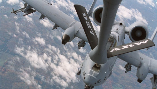An A-10 attack plane refuels while mated with a fuel delivery boom.