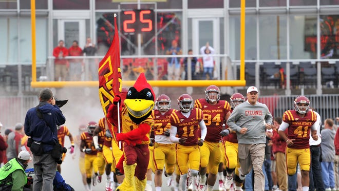 Iowa State Cyclones head coach Paul Rhoads (right center) leads his team out onto the field