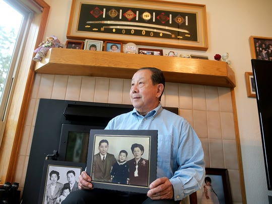 Dave Ojima was born at the Camp Harmony relocation center in Puyallup before his family was sent to an internment camp. He holds a photo of when he was a young boy in the camp with his parents.