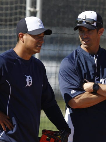 Tigers manager Brad Ausmus, right, talks with Jose