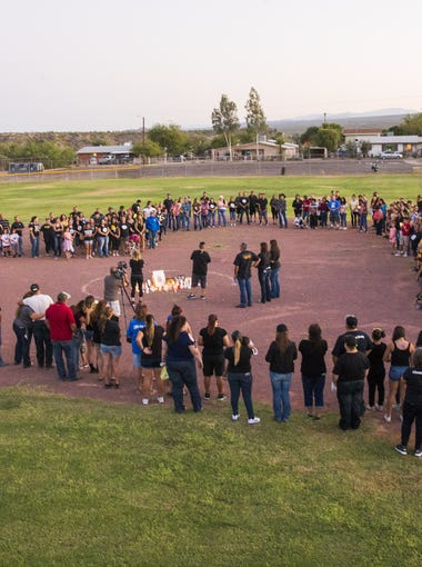 Family and friends make a heart around candles and pictures on the pitching circle during a candlelight vigil for Jovanna Martinez-Calzadillas at Hayden High in Winkelman on Oct. 8, 2017. Jovanna was critically injured in the Las Vegas shooting. She was a pitcher for the softball team when she went to high school.