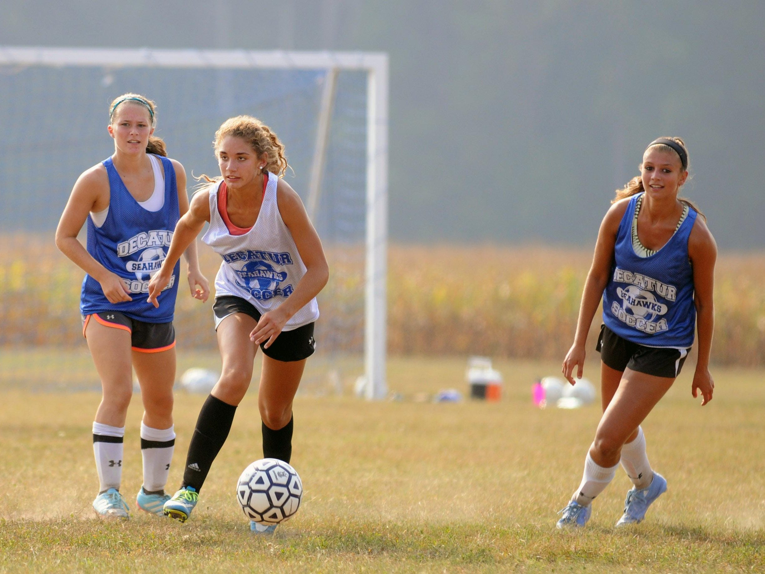 Stephen Decatur's Christina Romano, white, moves past two teammates during practice.