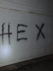 """A Sheridan police officer found the word """"HEX"""" spray-painted on a garage door on Tuesday."""