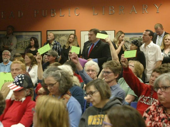 "Constituents at a listening session with U.S. Congressman Glenn Grothman hold up signs that read ""Agree"" or ""Disagree"" while the congressman answered questions."