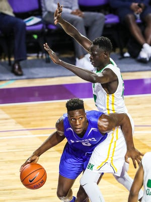 IMG's Emmitt Williams drives around The Patrick School's Buay Koka to score. IMG Academy and The Patrick School played Wednesday night in their City of Palms game to determine third place.