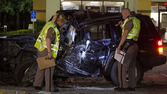 Florida Highway Patrol troopers examine the damage to a Jeep Cherokee involved in a fatal, mulitcar wreck Wednesday night on Lee Boulevard in Lehigh Acres.
