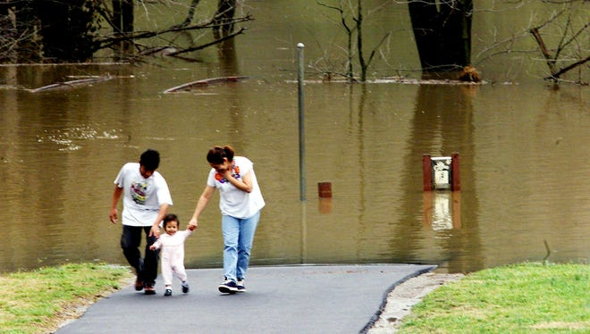 Nahum and Linda Rivera walk with their daughter Crystal at Pinkerton Park, which was partially flooded by the Harpeth River, on March 18, 2002.