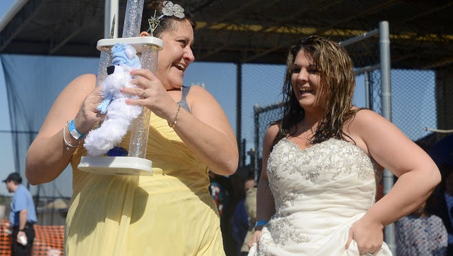 Terri Brakhage, left, and Falesha Vickers smile as they receive the trophy for best costume during the 6th annual Polar Plunge at Aloha Pools & Spas on Saturday, Feb. 27, 2016.