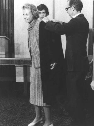 Judge Sandra Day O'Connor tries on her robes as an Arizona Court of Appeals judge in this 1979 photo. Helping her is her lawyer husband, John Jay O'Connor III. O'Connor was named by President Reagan to be the nation's first woman member of the U.S. Supreme Court.