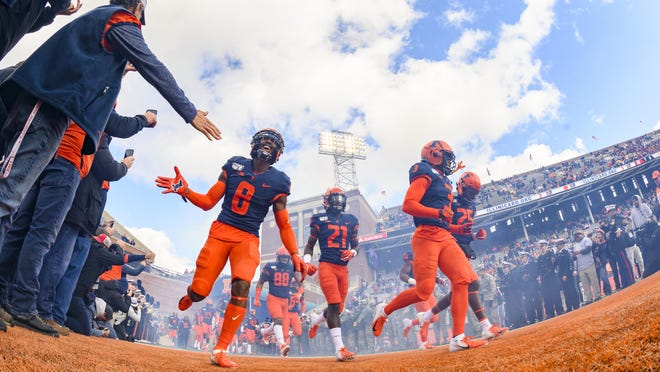 The Illinois football team runs onto the field prior to a game last season against Rutgers at Memorial Stadium in Champaign.