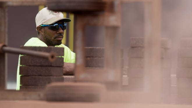 Decorative Paving Company employee Corey MacPherson of Indianapolis, Ind., stacks bricks for halving which will be used in the sidewalks and trails along North Main Street in Evansville Monday afternoon. Thousands of bricks will eventually be used in the project.