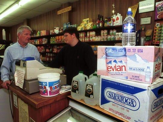 Robert Cavanaugh, owner of Cavanaugh's Grocery and Delicatessen on Leroy Street in Binghamton, talks with his son, Robert, inside the store in 1999.