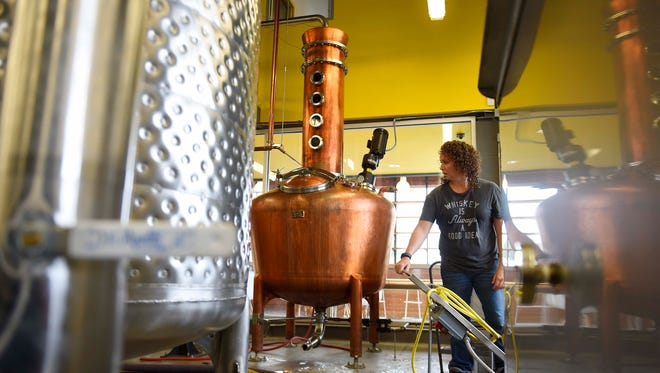 Distilling technician Rachael Sykes pumps water out of a container with a Vendome distiller pot behind her at Nashville Craft.