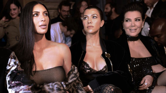 Kim Kardashian, Kourtney Kardashian and their mother Kris Jenner at a fashion show in Paris, Sept. 29, 2016. Reality television star Kim Kardashian was held at gunpoint on October 2, 2016 at a Paris hotel by assailants disguised as police officers, a spokesperson said. / AFP PHOTO / ALAIN JOCARDALAIN JOCARD/AFP/Getty Images ORIG FILE ID: AFP_GR4WP
