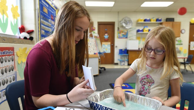 Using flash cards to display letters and sand to draw in, Mountain Home High School senior Annette Kasinger teaches the alphabet to Mountain Home kindergartener Marley Hodges Monday. On May 3, students in orientation to teaching II will be offered a paraprofessional assessment, allowing them to be certified by the time they graduate high school.