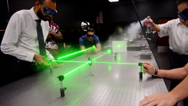 Electronic engineering technology students Michael Ferrer (from left), Christian Davis and Samuel Barrington work with a laser that can be used to measure extremely small distances, Thursday, April 27, 2017, in the LASER-TEC lab at Indian River State College in Fort Pierce. The National Science Foundation has awarded a $2.6 million Advanced Technology Education grant to the college to expand the LASER-TEC program.