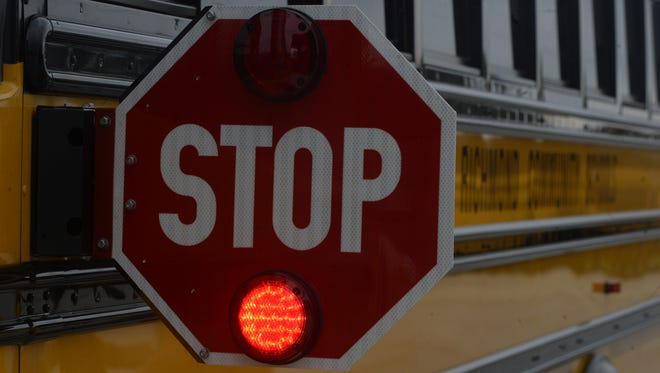 Drivers traveling in both directions must stop for a school bus stop arm unless there is a median, such as a grassy area, separating the lanes.