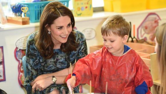 Work of art: Duchess Kate watches as kids fingerpaint.