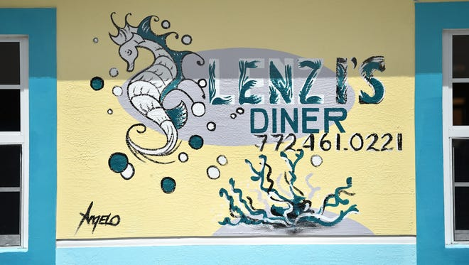 A mural representative of Lenzi's beach theme adorns the east wall along Ninth Street at the intersection with Avenue D in Fort Pierce on Thursday, July 19, 2018.