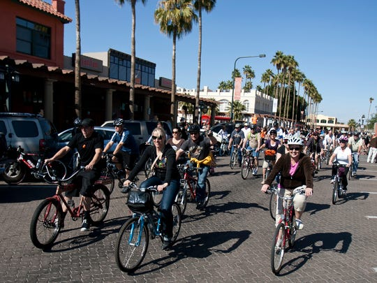 Bicyclists ride down San Marcos Place at the start