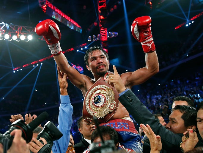 Manny Pacquiao wears the champion's belt after defeating Brandon Rios in their WBO international welterweight title fight Sunday, Nov. 24, 2013, in Macau.